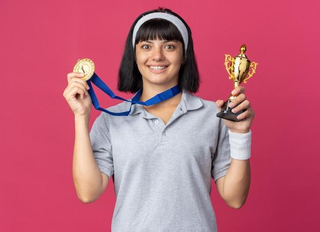 Szczęśliwa młoda dziewczyna fitness nosząca opaskę ze złotym medalem na szyi trzymająca trofeum