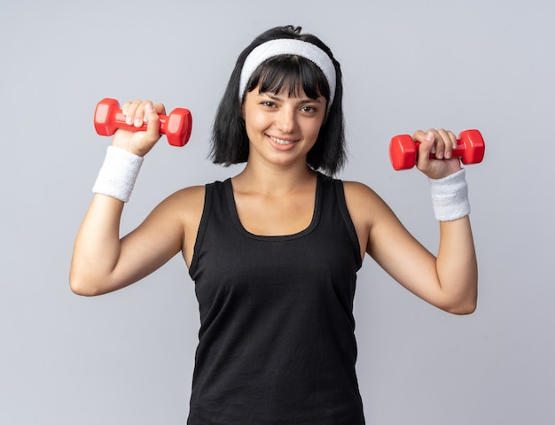 Szczęśliwa młoda dziewczyna fitness ubrana w opaskę, trzymająca hantle, wykonująca ćwiczenia, wyglądająca pewnie uśmiechnięta