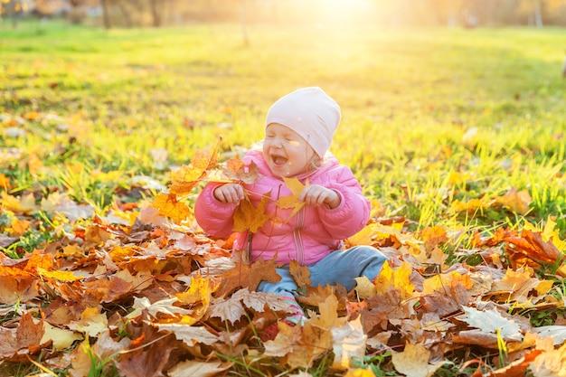 Szczęśliwa młoda dziewczyna gra pod spadającymi żółtymi liśćmi w pięknym jesiennym parku na spacery na świeżym powietrzu. małe dziecko rzuca jesienne pomarańczowe liście klonu. witam koncepcja jesień.