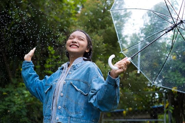 Szczęśliwa młoda dziewczyna gra z deszczem w zielonym ogrodzie.
