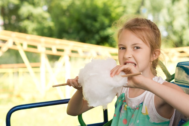 Szczęśliwa młoda dziewczyna je watę cukrową na targach