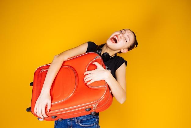 Szczęśliwa młoda dziewczyna jedzie na wakacje, trzymając dużą ciężką czerwoną walizkę, podróżuje