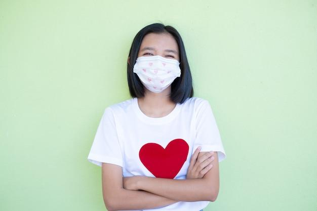 Szczęśliwa młoda dziewczyna nosi maskę i białą koszulę z czerwonym sercem.