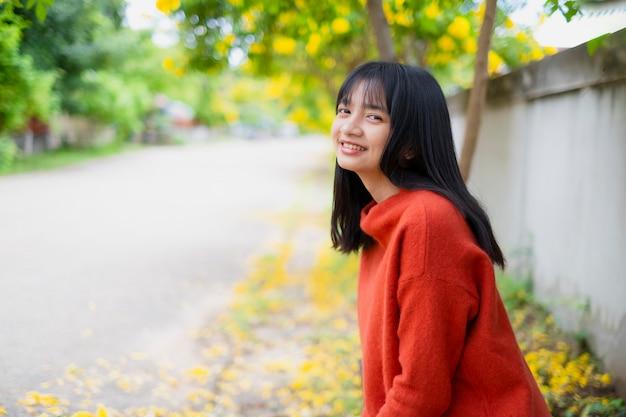 Szczęśliwa młoda dziewczyna nosić pomarańczowy sweter pod drzewem i żółty kwiat.