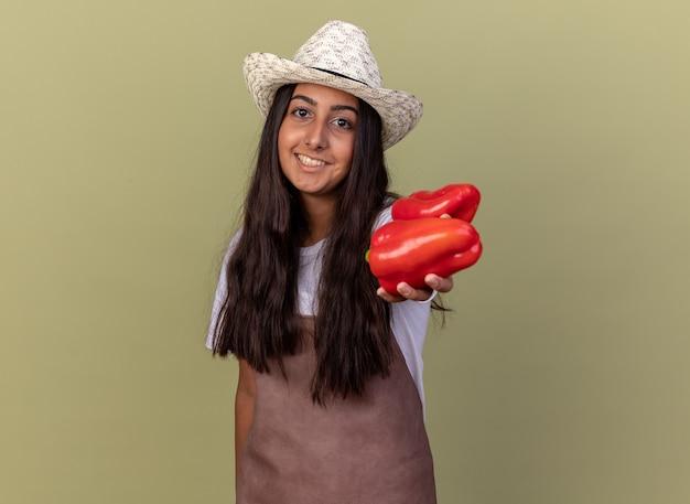 Szczęśliwa młoda dziewczyna ogrodnik w fartuch i letni kapelusz pokazuje świeże czerwone papryki z uśmiechem na twarzy stojącej nad zieloną ścianą