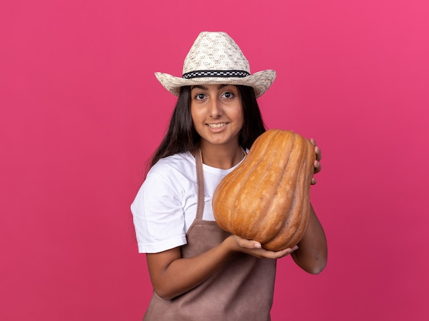 Szczęśliwa młoda dziewczyna ogrodnik w fartuch i letni kapelusz trzymając dyni z uśmiechem na twarzy stojącej nad różową ścianą
