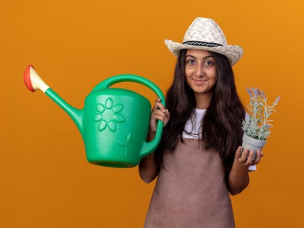 Szczęśliwa młoda dziewczyna ogrodnik w fartuch i letni kapelusz trzymając konewkę i roślina doniczkowa z uśmiechem na twarzy stojącej nad pomarańczową ścianą