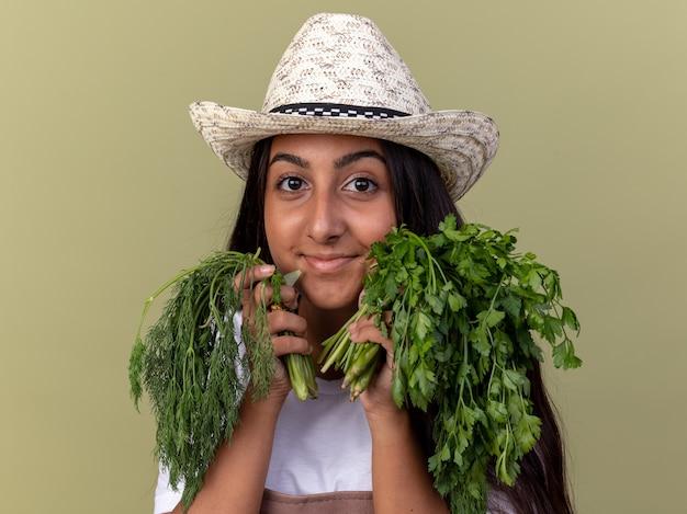 Szczęśliwa młoda dziewczyna ogrodnik w fartuch i letni kapelusz trzymając świeże zioła z uśmiechem na twarzy stojącej nad zieloną ścianą