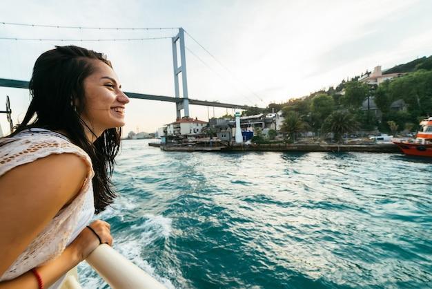 Szczęśliwa młoda dziewczyna podróżnik uśmiecha się w pełnym widoku, zachód słońca nad bosforem. nowoczesny most
