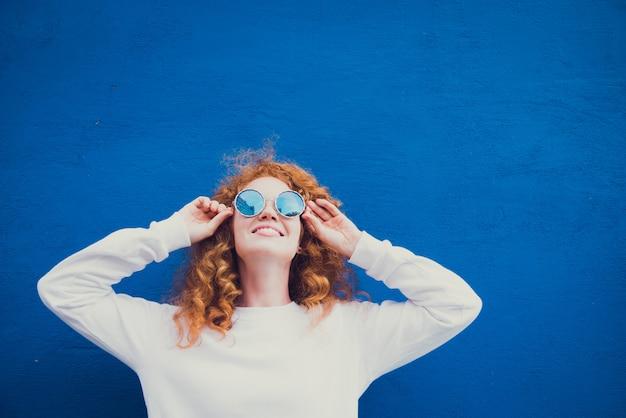 Szczęśliwa młoda dziewczyna pozuje w okularach przeciwsłonecznych na błękitnym tle