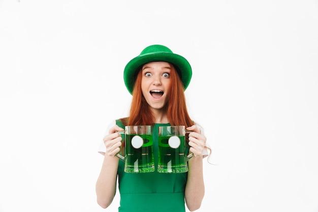 Szczęśliwa młoda dziewczyna redheaded w zielonym kapeluszu, obchodzi dzień świętego patryka na białym tle nad białą ścianą, pijąc piwo