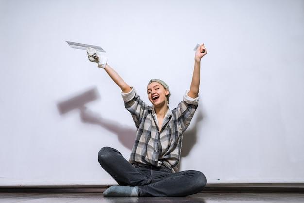 Szczęśliwa młoda dziewczyna siedzi na podłodze w swoim nowym mieszkaniu, trzyma łopatkę, naprawia