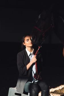 Szczęśliwa młoda dziewczyna siedzi outdoors ściskający jej konia