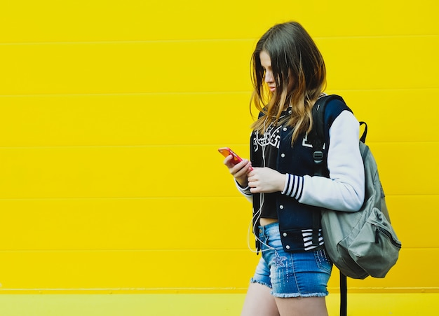Szczęśliwa młoda dziewczyna słuchania muzyki w słuchawkach