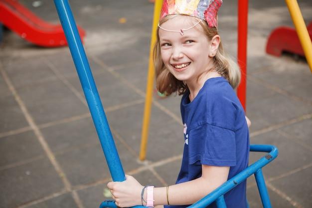 Szczęśliwa młoda dziewczyna śmiejąca się radośnie, siedząca na huśtawce na placu zabaw