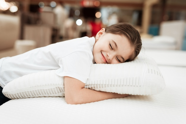 Szczęśliwa młoda dziewczyna śpi z poduszką na materacu