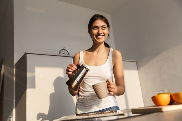 Szczęśliwa młoda dziewczyna stojąc w kuchni rano, po filiżance kawy