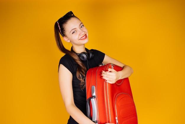 Szczęśliwa młoda dziewczyna trzyma dużą czerwoną walizkę, jedzie na wakacje, uśmiechając się