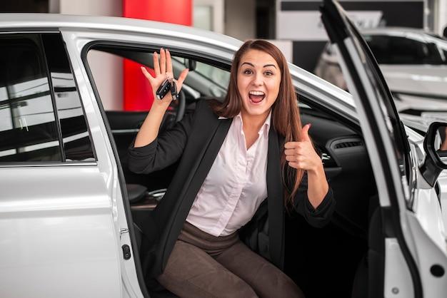 Szczęśliwa młoda dziewczyna trzyma kluczyki do samochodu