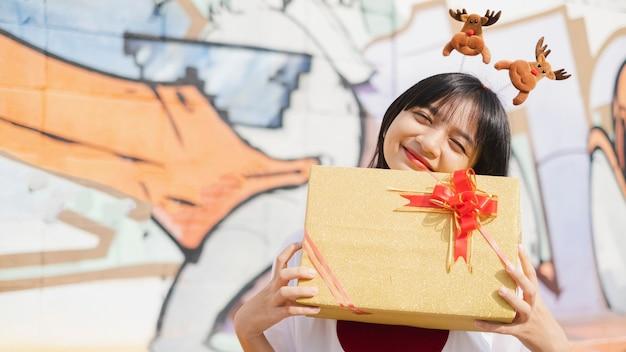 Szczęśliwa młoda dziewczyna trzyma obecne pudełko na kolorowym tle. azjatycka młoda dziewczyna.