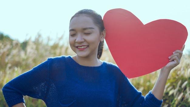 Szczęśliwa młoda dziewczyna trzyma papierowe czerwone serce na łące azjatycka dziewczyna
