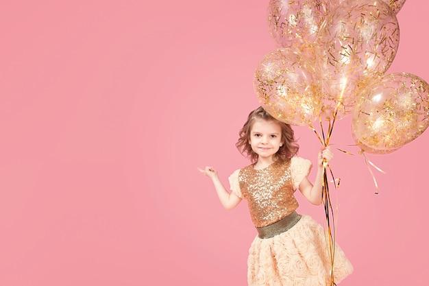Szczęśliwa młoda dziewczyna trzyma wiązkę balony