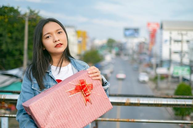 Szczęśliwa młoda dziewczyna trzymać pudełko na tle widoku miasta.