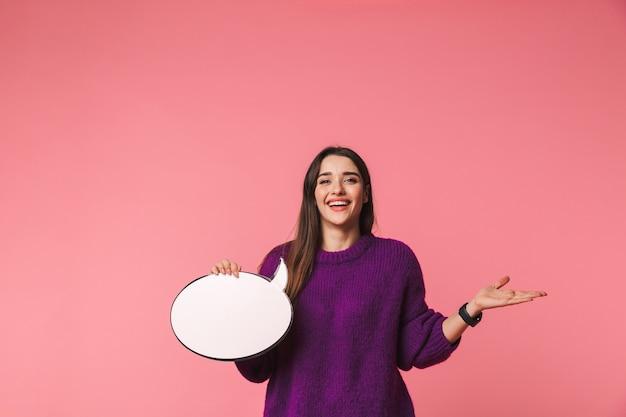 Szczęśliwa młoda dziewczyna ubrana w sweter stojący na białym tle nad różowym, trzymając pusty dymek