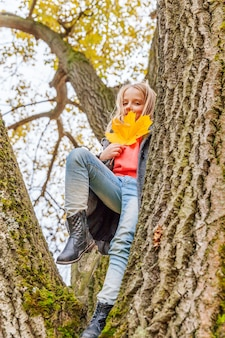 Szczęśliwa młoda dziewczyna uśmiecha się i siedzi na drzewie w pięknym jesiennym parku na spacery na świeżym powietrzu. małe dziecko grając w jesień jesień pomarańczowy żółty tło. witam koncepcja jesień.