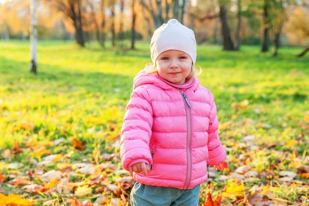 Szczęśliwa młoda dziewczyna uśmiechając się w pięknym jesiennym parku na spacery natury. małe dziecko grając w jesień jesień pomarańczowy żółty tło. witam koncepcja jesień.