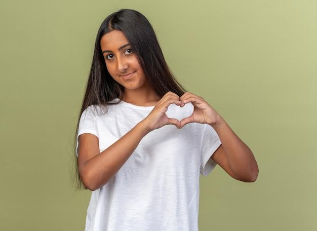 Szczęśliwa młoda dziewczyna w białej koszulce patrząca na kamerę, która robi gest serca palcami uśmiechając się radośnie stojąc nad zielenią