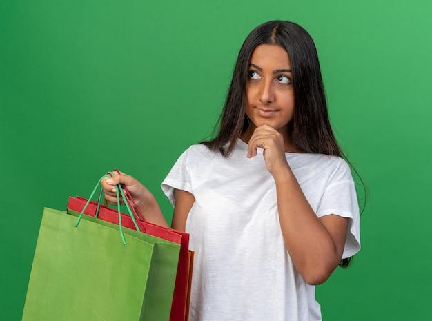 Szczęśliwa młoda dziewczyna w białej koszulce trzymająca papierowe torby patrząc na bok z ręką na brodzie z zamyślonym wyrazem twarzy
