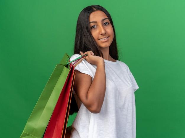 Szczęśliwa młoda dziewczyna w białej koszulce trzymająca papierowe torby patrząc na kamerę z uśmiechem na twarzy