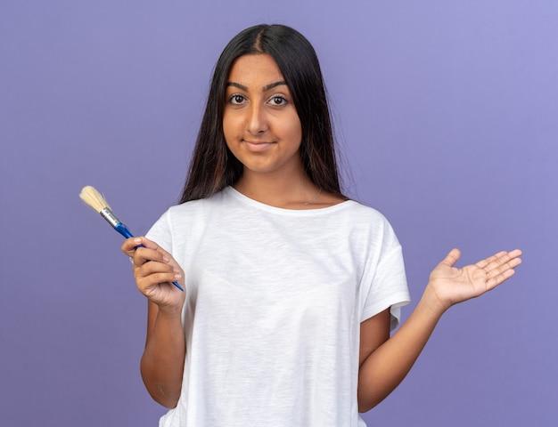 Szczęśliwa młoda dziewczyna w białej koszulce trzymająca pędzel patrząc na kamerę z uśmiechem na twarzy stojącej na niebieskim tle