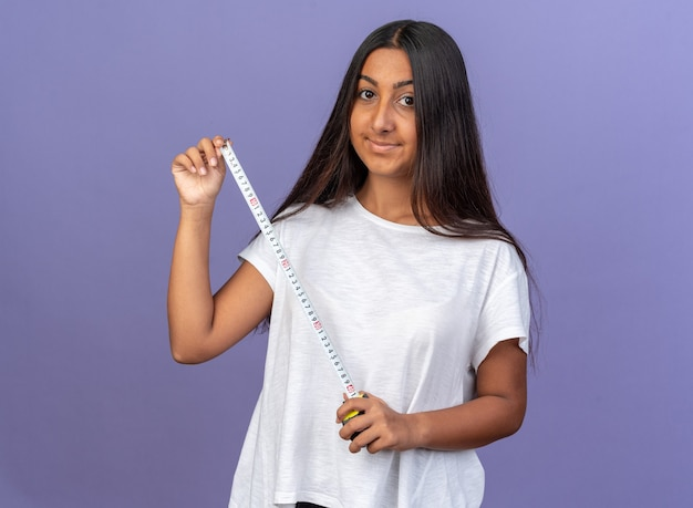 Szczęśliwa młoda dziewczyna w białej koszulce trzymającej taśmę mierniczą patrząc na kamerę z uśmiechem na twarzy stojącej na niebieskim tle