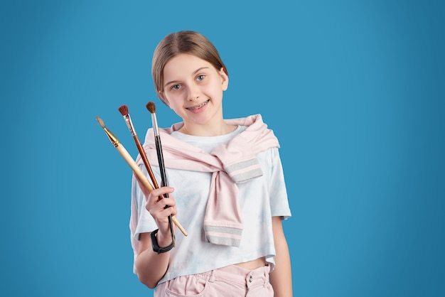 Szczęśliwa młoda dziewczyna w casual, pokazując kolekcję pędzli do profesjonalnego malowania, stojąc na niebieskim tle