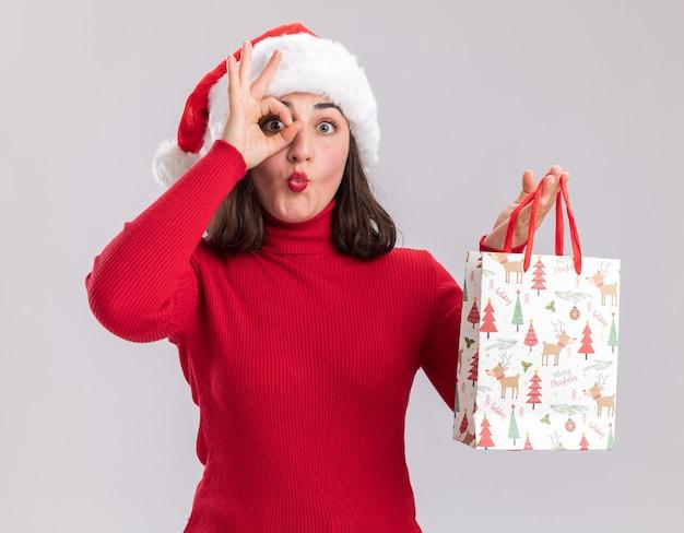 Szczęśliwa młoda dziewczyna w czerwonym swetrze i czapce mikołaja trzyma kolorową papierową torbę z prezentami świątecznymi, robiąc znak ok, patrząc przez ten znak stojąc na białym tle