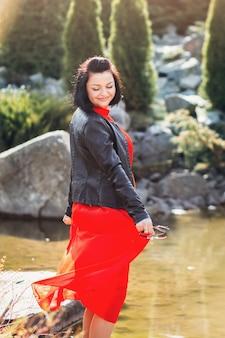Szczęśliwa młoda dziewczyna w długiej sukni stoi nad brzegiem jeziora. kobieta cieszy się naturą