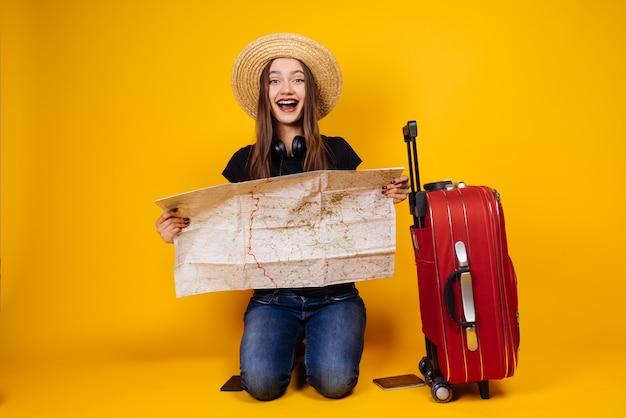 Szczęśliwa młoda dziewczyna w kapeluszu pojechała na wycieczkę odpocząć, z walizką i mapą