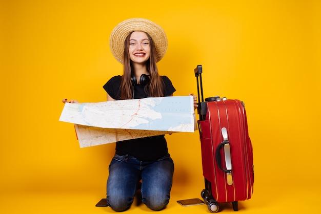 Szczęśliwa młoda dziewczyna w kapeluszu trzymająca kartkę, jadąca na wycieczkę z walizką