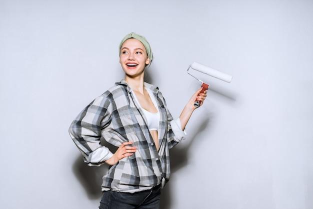 Szczęśliwa młoda dziewczyna w kraciastej koszuli koloruje ścianę talerzem w swoim nowym mieszkaniu