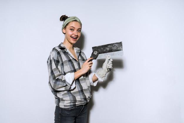 Szczęśliwa młoda dziewczyna w kraciastej koszuli trzymająca łopatkę, robiąca naprawy w swoim nowym mieszkaniu