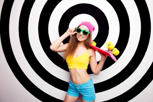 Szczęśliwa młoda dziewczyna w okularach i różowej czapce gospodarstwa skate