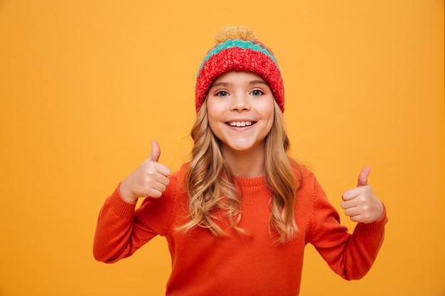Szczęśliwa młoda dziewczyna w pulowerze i kapeluszu pokazuje aprobaty i patrzeje kamerę nad pomarańcze