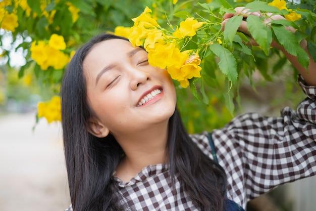 Szczęśliwa młoda dziewczyna z pięknym żółtym kwiatem.