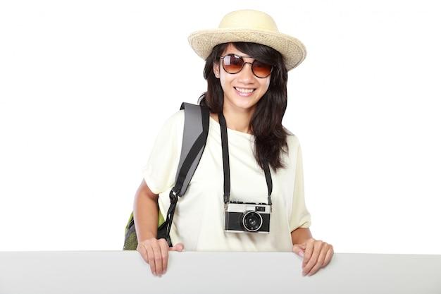 Szczęśliwa młoda dziewczyna z plecakiem pokazuje puste miejsce deskę