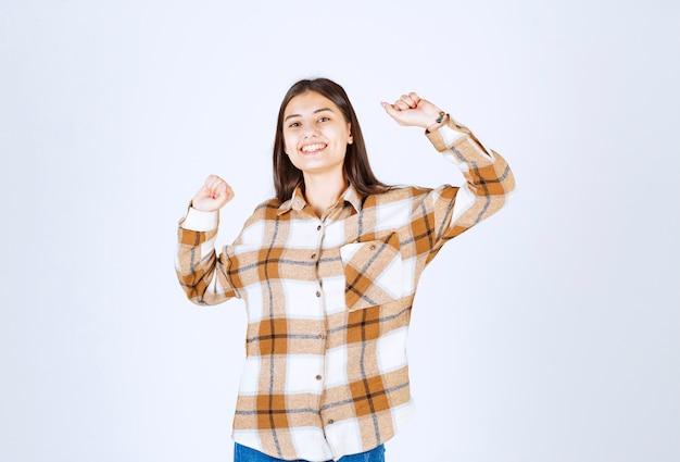Szczęśliwa młoda dziewczyna z pozowanie z podnoszeniem rąk.