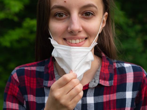 Szczęśliwa młoda dziewczyna zdejmuje maskę medyczną i oddycha świeżym powietrzem w przyrodzie