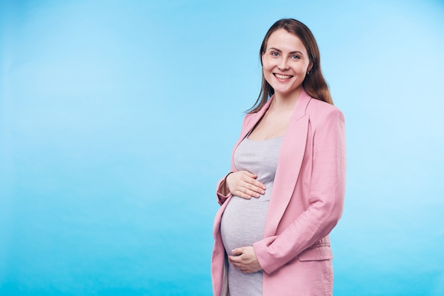 Szczęśliwa młoda elegancka przyszła matka w szarej casualowej sukience i różowym płaszczu, trzymając ręce na brzuchu, stojąc w izolacji