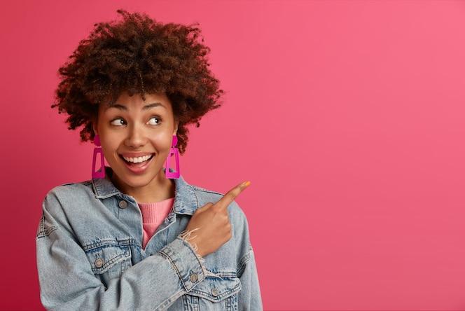 Szczęśliwa młoda, entuzjastyczna kobieta w modnych ubraniach wskazuje puste miejsce, wskazuje drogę do kawiarni lub restauracji, reklamuje najlepsze kursy online, demonstruje dobry pomysł na zakupy. twoja promocja lub reklama tutaj